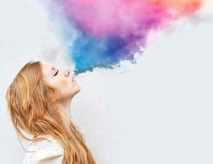 Dziewczyna wydmuchująca kolorowy dym