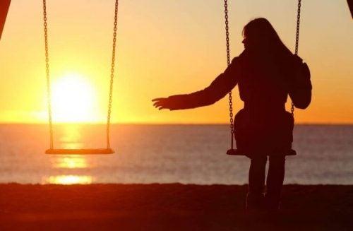 Dziewczyna na siedzi na huśtawce, a obok puste miejsce