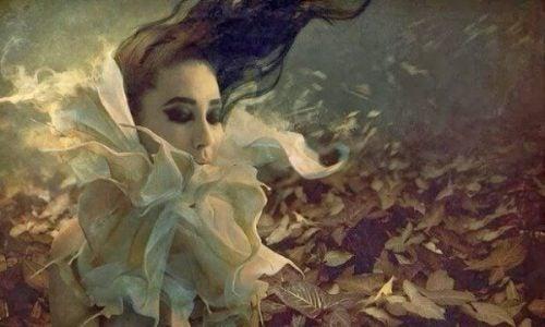 Emocje - smutna dziewczyna wśród liści