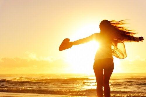 Dziewczyna na plaży patrzy na zachód słońca