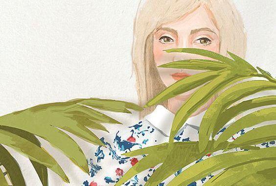 Dziewczyna ukryta za liśćmi palmy.