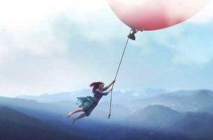 Dziewczynka lata trzymając się wielkiego balonu - odkryć się na nowo