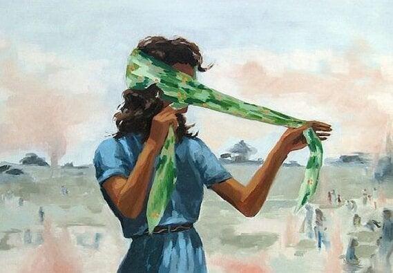 Kobieta owija twarz szalem.