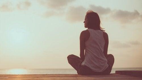 Kobieta siedzi na ziemi i patrzy przed siebie