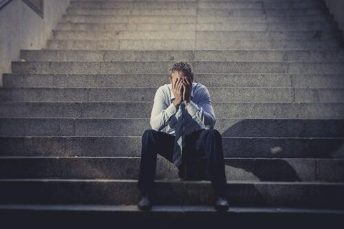 Załamany mężczyzna na schodach - bezrobocie