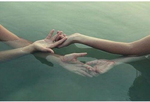 Dwie osoby trzymają się za ręce pod wodą