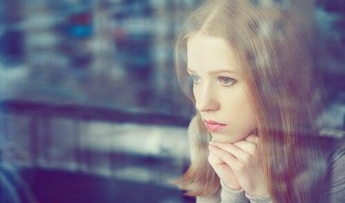 Smutna dziewczyna wygląda przez okno.