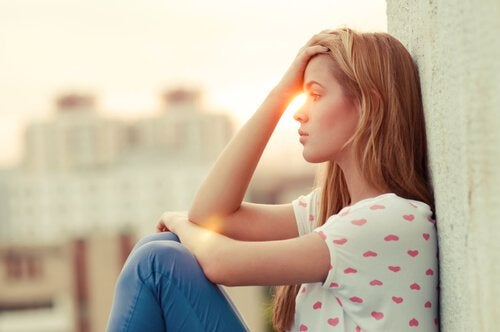 Smutna kobieta siedzi pod ścianą