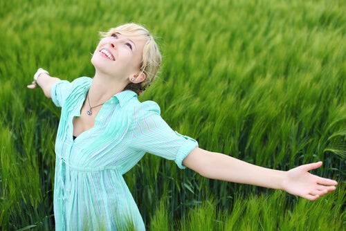 Szczęśliwa kobieta rozkłąda rece na zielonej trawie