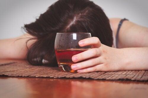 Alkoholiczka na podłodze trzyma kieliszek wina