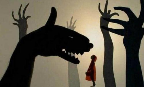 Czerwony kapturek i ręka rzucająca cień w kształcie wilka