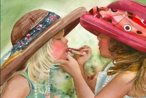 Jedna dziewczynka maluje szminką usta drugiej