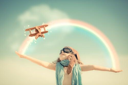 Dziecko i samolot lecący po tęczy.