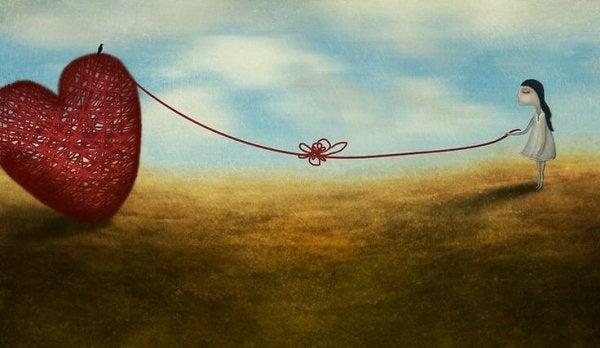 Dziewczynka trzyma serce na sznurku.