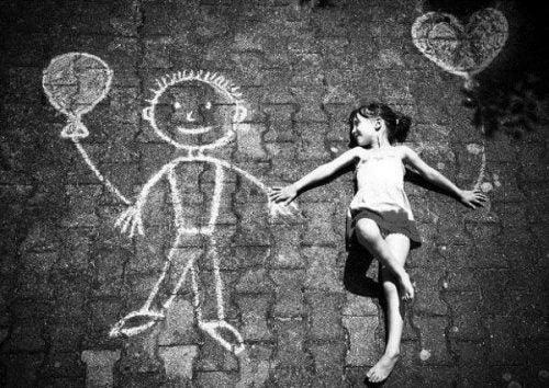 Dziewczynka leży na asfalcie obok narysowanego chłopca