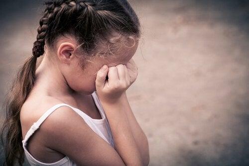 Dziewczynka płacze, zakrywając twarz dłońmi