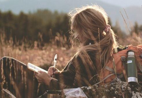 Kobieta pisze list w polu zboża