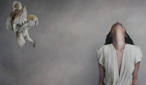 Kobieta patrząca w górę i sowa