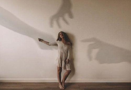 Kobieta przy ścianie i cienie