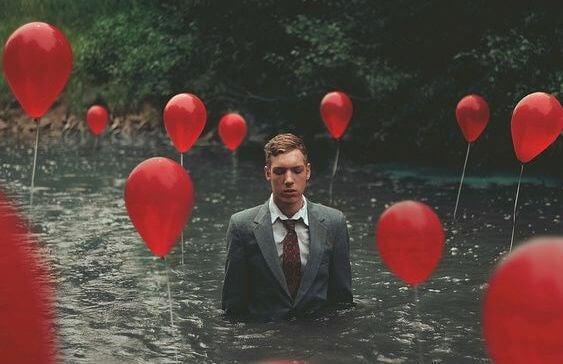 Mężczyzna w wodzie z czerwonymi balonikami.
