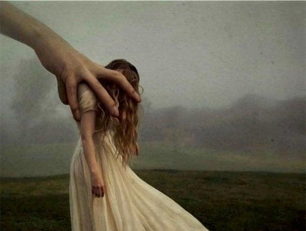 Ręka popychająca dziewczynę.