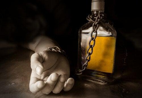 Ręka przykuta do butelki z alkoholem