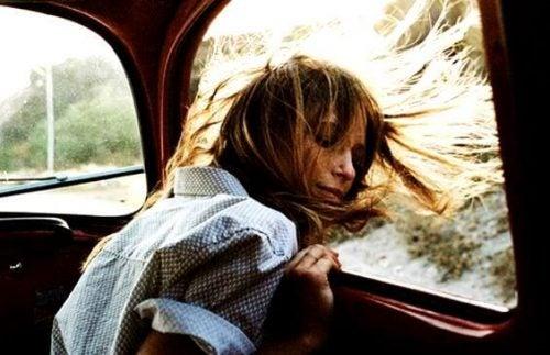 Szczęśliwa dziewczyna z rozwianymi włosami przy oknie w samochodzie