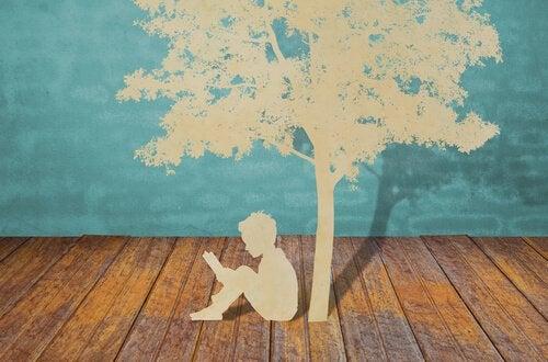 Papierowy chłopiec czytający pod drzewem.