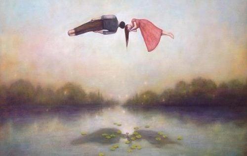Dwie osoby unoszą się nad wodą przytulając się głowami