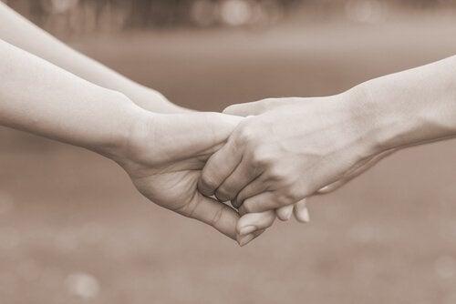 Dwie osoby trzymają się za ręce