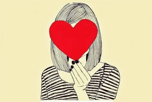 Dziewczyna zasłania twarz sercem