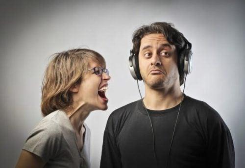Ignorowanie problemu - kobieta krzyczy, mężczyzna słucha muzyki
