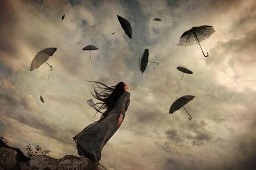 Dziewczyna patrząca na latajace parasole.