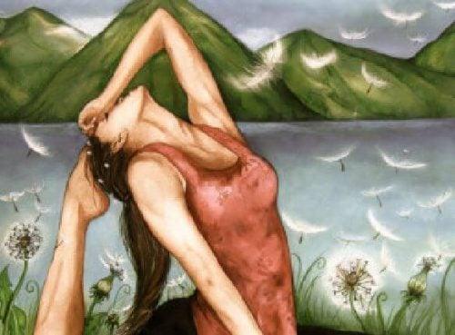 Kobieta praktykuje jogę nad jeziorem