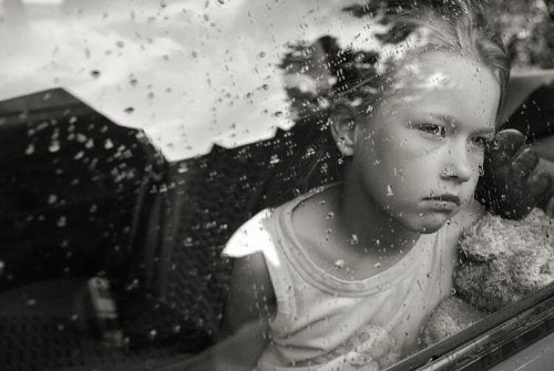 Mała dziewczynka smutno patrzy przez okno