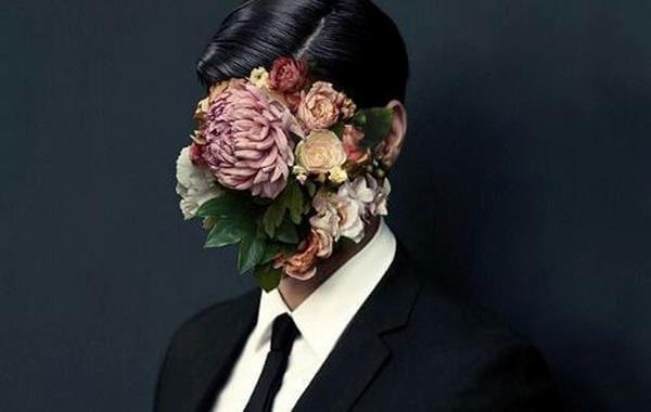 Mężczyzna z twarzą zakryta kwiatami.