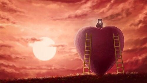 Para ogląda zachód słońca siedząc na wielkim sercu