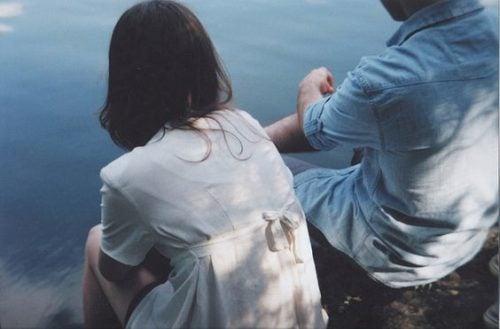 Para siedzi nad wodą i prowadzi rozmowę