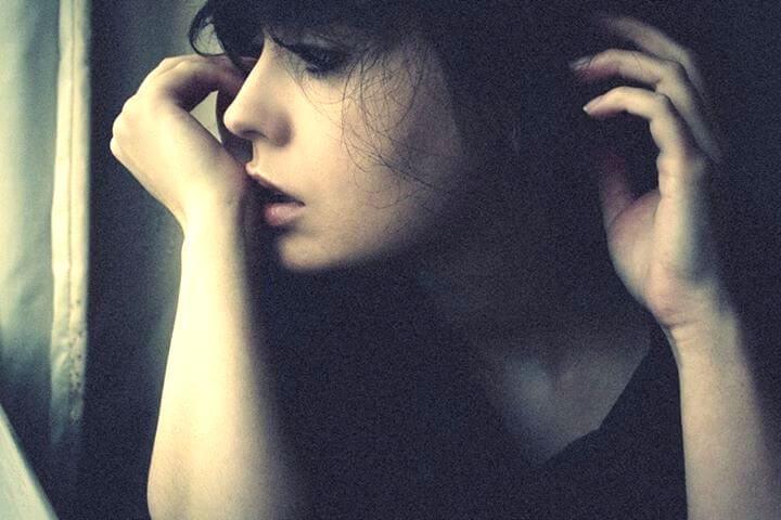 Smutna kobieta patrzy przez okno.