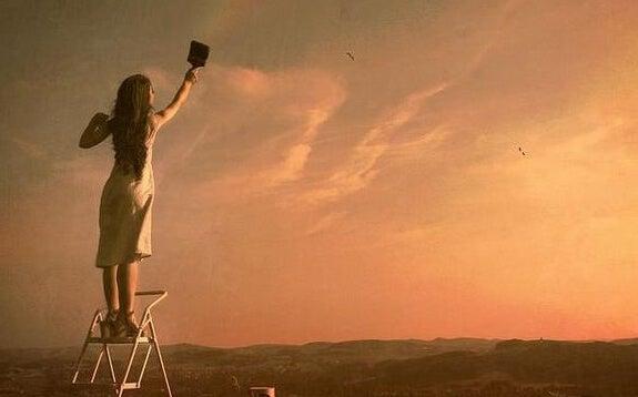 Kobieta na drabinie malująca niebo