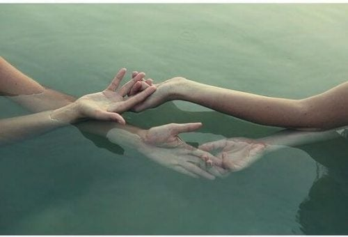 Pieszczoty - dwie pary rąk w wodzie