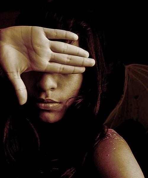 Dziewczyna zasłania ręką twarz