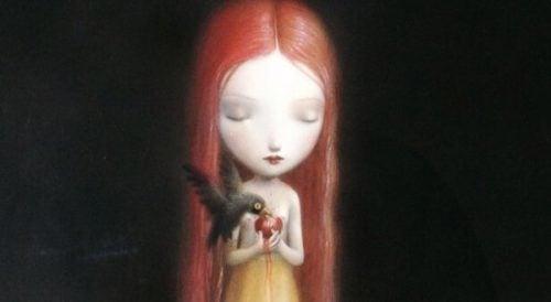 Dziewczyna trzyma jabłko, które dziobie ptak