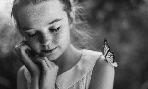 Dziewczynka z motylem na ramieniu.