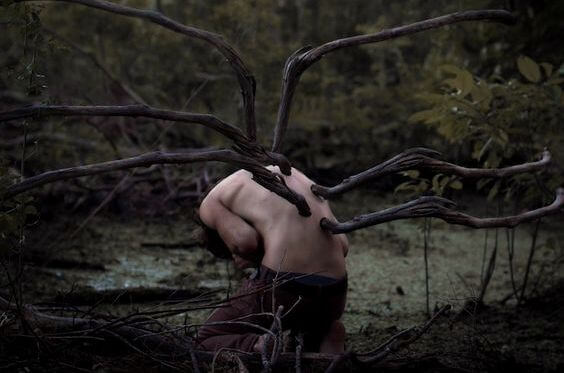 Mężczyzna, któremu z pleców wyrastają gałęzie.