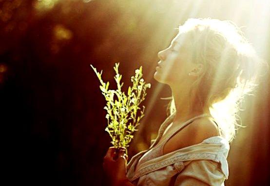 Kobieta z rośliną w ręku cieszy się słońcem
