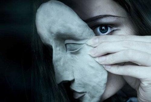 Kobieta ściągająca maskę z twarzy.