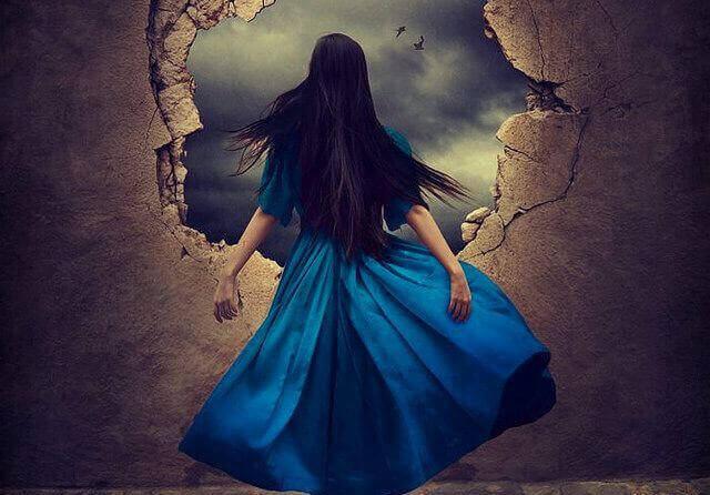 Dziewczyna wychodzi przez dziurę w ścianie.
