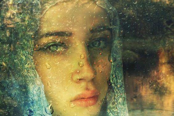 Dziewczyna za szybą spłakaną deszczem.