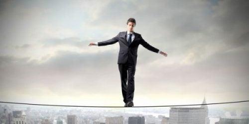 Człowiek idzie po linie nad miastem